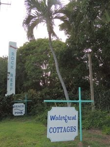Road signs. Text: Rock Reef, Waterfront Cottages.